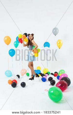 Young girl posing on fancy background after bright school party with close friends. Fun times