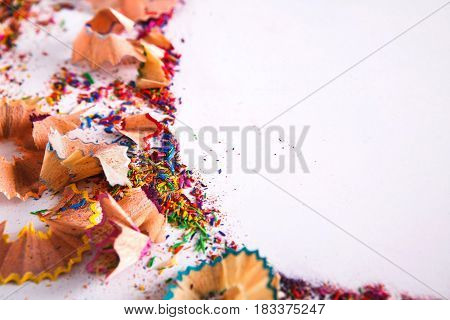 Wooden colored pencil sharpening shavings frame on white isolated background, top view, flat lay, copy space