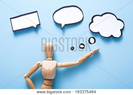 Handcrafted wooden man doll with blank speech bubble on blue background, objects, nobody