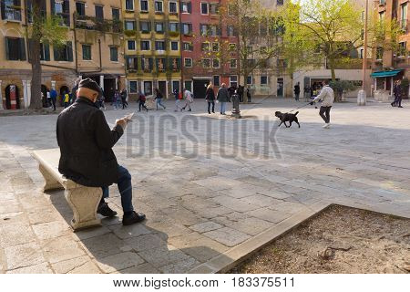 VENICE ITALY - APRIL 2 2017: Morning at Campo del Ghetto Nuovo (Jewish ghetto). An elderly men is reading a newspaper while tourists are gathering to visit the place.