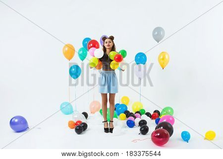 Pretty young woman in fashion clothing posing with colourful helium balloons at dancing place