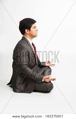 front view of an indian young businessman meditating or practicing yoga or pranayama or breathing exercise in corporate attire in the office or isolated over white background