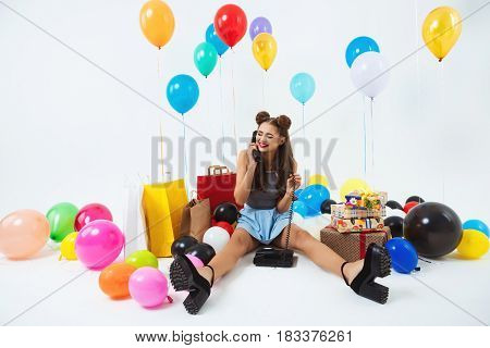Beautiful young woman with phone receiver in hands, recieving birthday wishes, looking down blushing, smiling