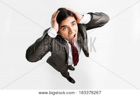 indian businessman having headache or holding head in frustration or depression, isolated over white background, bird's eye view or view from top