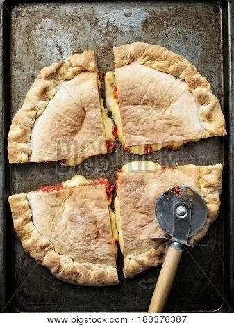 close up of rustic italian calzone stuffed pizza