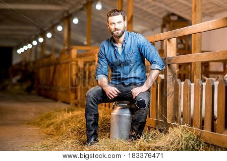 Portrait of a handsome farmer sitting on the retro milk container at the goat barn. Natural milk production and farming concept