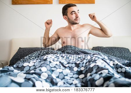 Young Man Stretching On Bed In Bedroom At Home
