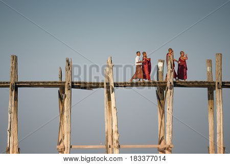 AMARAPURA MYANMAR - DECEMBER 23 2016 : Buddhist monks and local people walking on U Bein Bridge the oldest and longest teak bridge (Wooden footbridge) in the world near Mandalay.