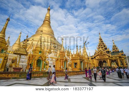 YANGON MYANMAR - DECEMBER 17 2016 : Unidentified Burmese people walk inside the area of Shwedagon pagoda (Shwedagon Zedi Daw) famous landmark and travel destination of Yangon Myanmar.