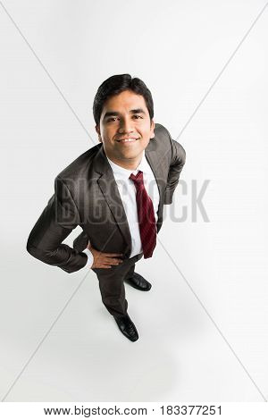 indian young & handsome businessman in clean shave and office wear standing, looking up / in the sky, a view from top also known as bird's eye view showing perspective, isolated over white background