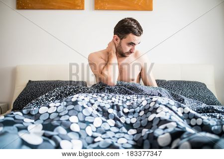 Young Man Suffering From Neckache In Bedroom At Home