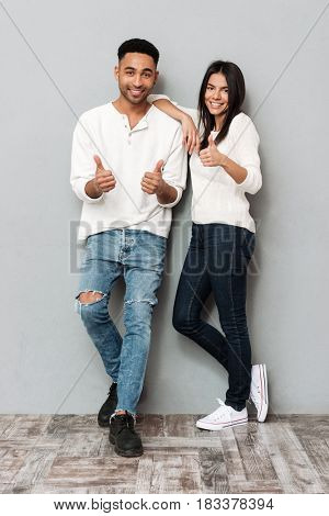 Image of happy young loving couple standing over grey wall and looking at camera. Showing thumbs up.