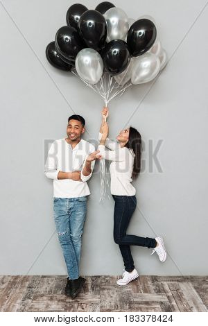 Photo of young happy loving couple standing over grey wall while holding balloons.