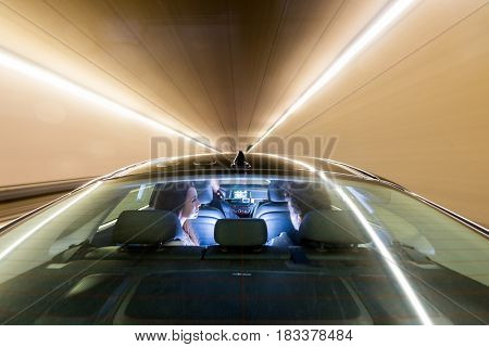 Blurred motion of male taxi driver riding couple in illuminated tunnel