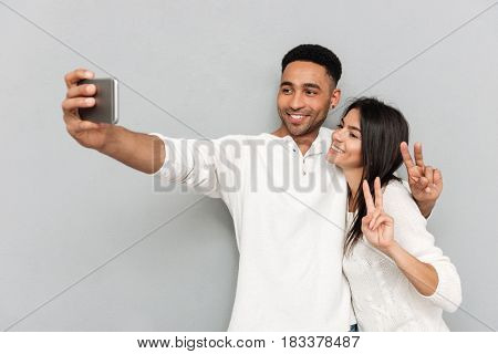 Cheerful couple making selfie on smartphone and smiling isolated