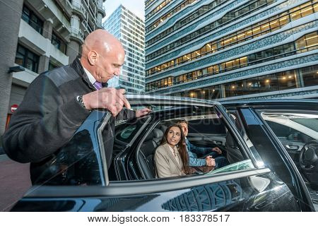 Professional male taxi driver opening car door for male and female passengers in city