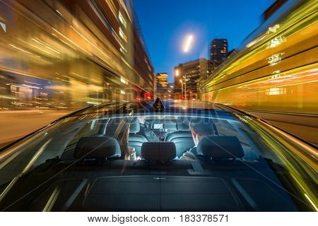 Blurred motion of professional male taxi driver riding couple on city street at night