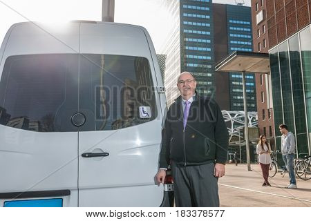 Portrait of confident professional taxi driver standing by van at airport