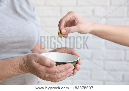 Female hand putting coin into bowl in hands of senior woman, closeup. Poverty concept