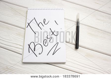 A notebook with an inscription is the best and black marker on white wooden table