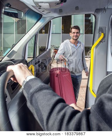 Smiling man, carrying a suitcase, entering a minivan, on his way to the airport, his eyes meeting and greeting the bus driver.