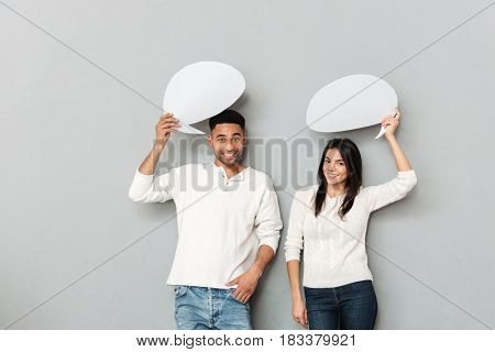 Smiling pretty couple holding blank bubbles over head isolated
