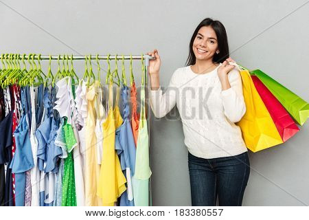 Image of young happy lady standing over grey wall while holding shopping bags and looking at camera.