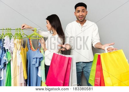 Image of young confused man holding shopping bags while his woman choosing clothes over grey wall.