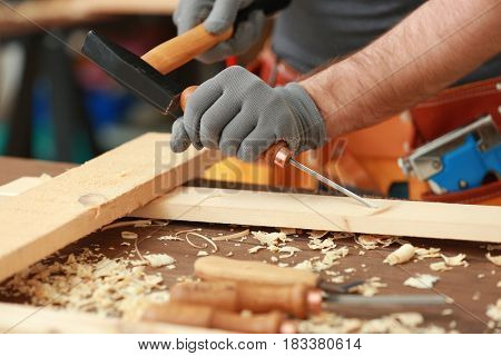 Carpenter with chisel and hammer in workshop, closeup