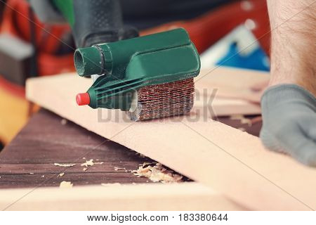 Carpenter with electrical grinder in workshop, closeup