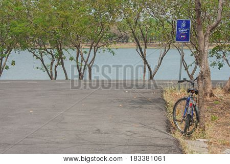 Bicycle lean tree near bicycle lane with lake background. Foreign text on the signs is mean