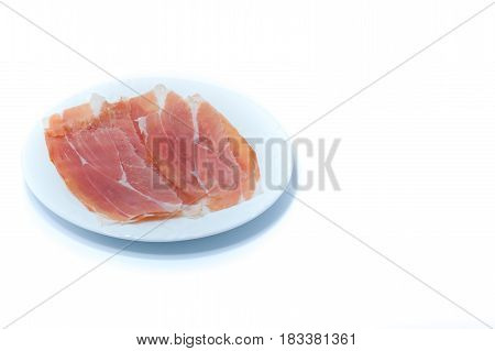 Raw Ham Prosciutto In A White Dish Isolated On White Background