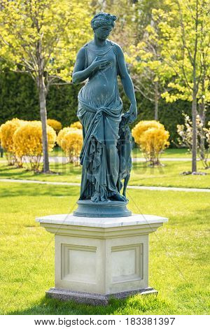 Statue of Goddess in a Classical Style. Antic statue of the Nymph with dog in the park