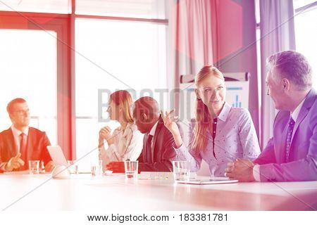 Young businesswoman discussing with male colleague in board room