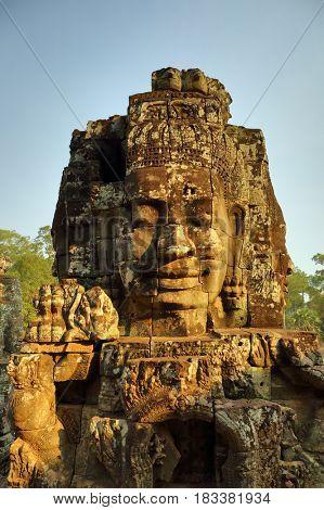 Giant stone faces at Bayon Temple at sunset, Angkor Wat, Cambodia
