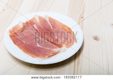 Raw Dried Cured Ham Prosciutto In A White Dish Isolated On A Pine Wood Board