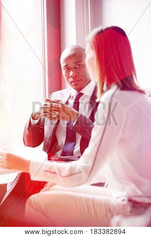 Young businessman with female colleague in office cafeteria