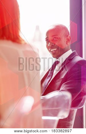 Young businessman talking with female colleague in office cafeteria