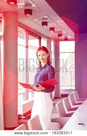 Portrait of confident young businesswoman holding file in conference room