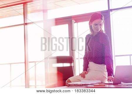 Young businesswoman using laptop while sitting on desk in office