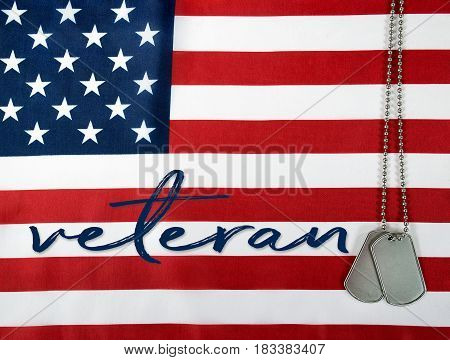 word veteran and military dog tags on American flag