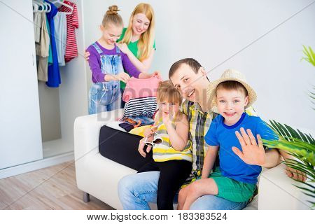 Happy family going on vacation packing suitcases for a trip