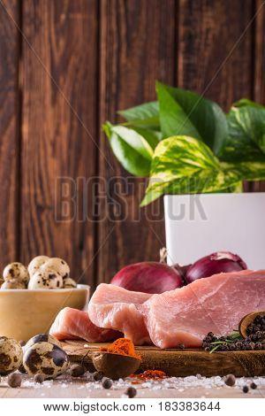 Few Slices Of Raw Pork Meat On Dark Wooden Plate