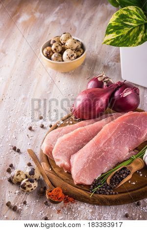 Three Slices Of Raw Pork Meat On Wooden Plate