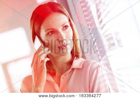 Close-up of young businesswoman using mobile phone while looking through office window
