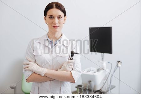 I am expert. Attractive female standing in foreground of the consulting room crossing her hands on the chest while looking straight at camera