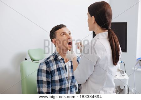 It is very good. Male patient sitting on green chair keeping his mouth wide opened being at consulting room