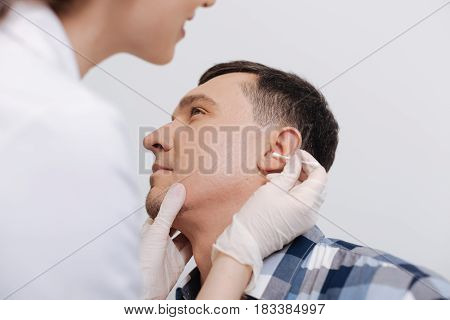 You should clean it. Young doctor using cotton bud in right hand while looking into ear of her patient