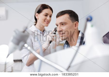 Do it quickly. Attentive competent otolaryngologist wearing rubber gloves keeping smile on her face while examining hearing