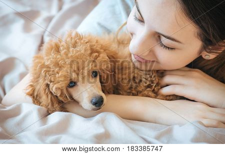 Young woman is lying and sleeping with poodle dog in bed.